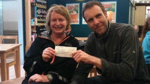 Jean Bryson passes donation cheque to Paul Kerr of Happy Dayz
